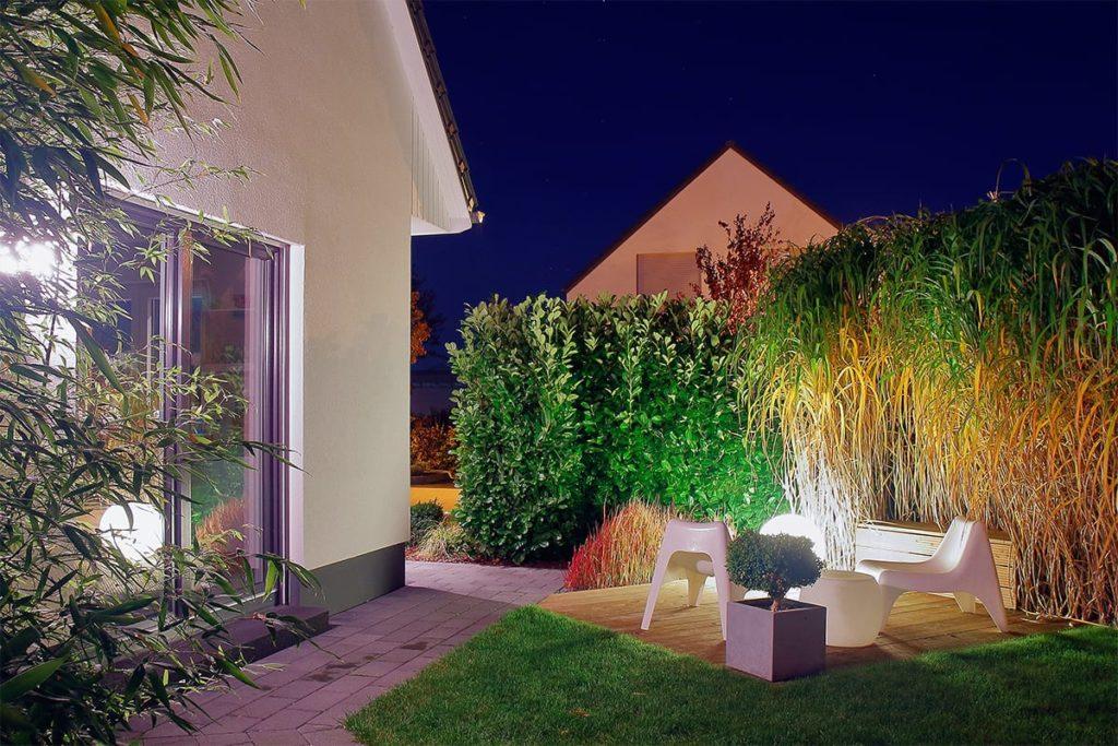 Beleuchteter Garten von Plan2Grün hinter einem Einfamilienhaus