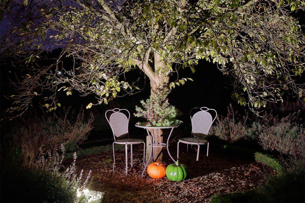 Gartenstühle und Gartentisch an einem Baum im beleuchteten Garten von Plan2Grün