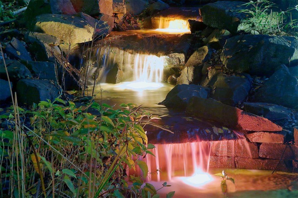 Beluchteter Wasserfall in einem Garten von Plan2Grün