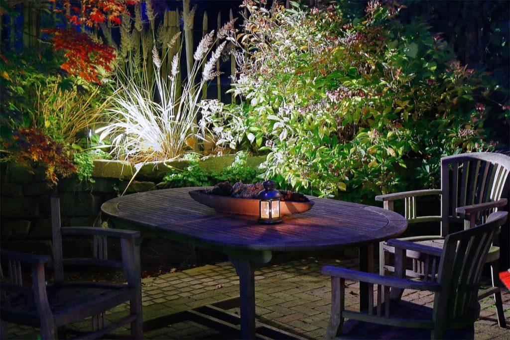 Gartentisch und Gartenstühle bei Nacht in einem beleuchteten Garten von Plan2Grün